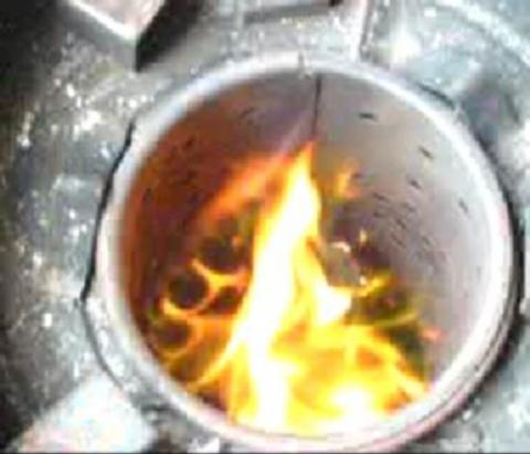 Here is an example (hard to see of course because it is a still taken from a video) of the spinning of the flame caused by the shaped grate at the bottom.